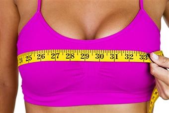 Woman measuring breasts in halter top