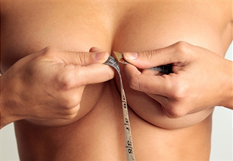 Woman measuring medium sized breasts