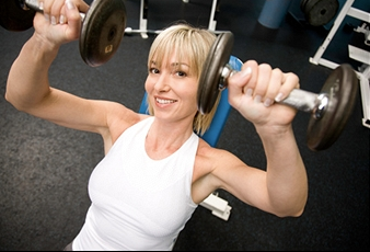 Middle aged women performing dumbbell press