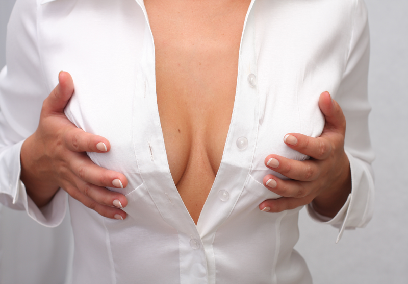 Breast Enlargement Benefits - Woman In White Blouse holding Breasts